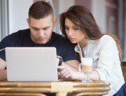 Portrait of young man and woman in casual clothes sitting in street cafe with rattan furniture drinking coffee, working on laptop, looking at screen with serious focused expression