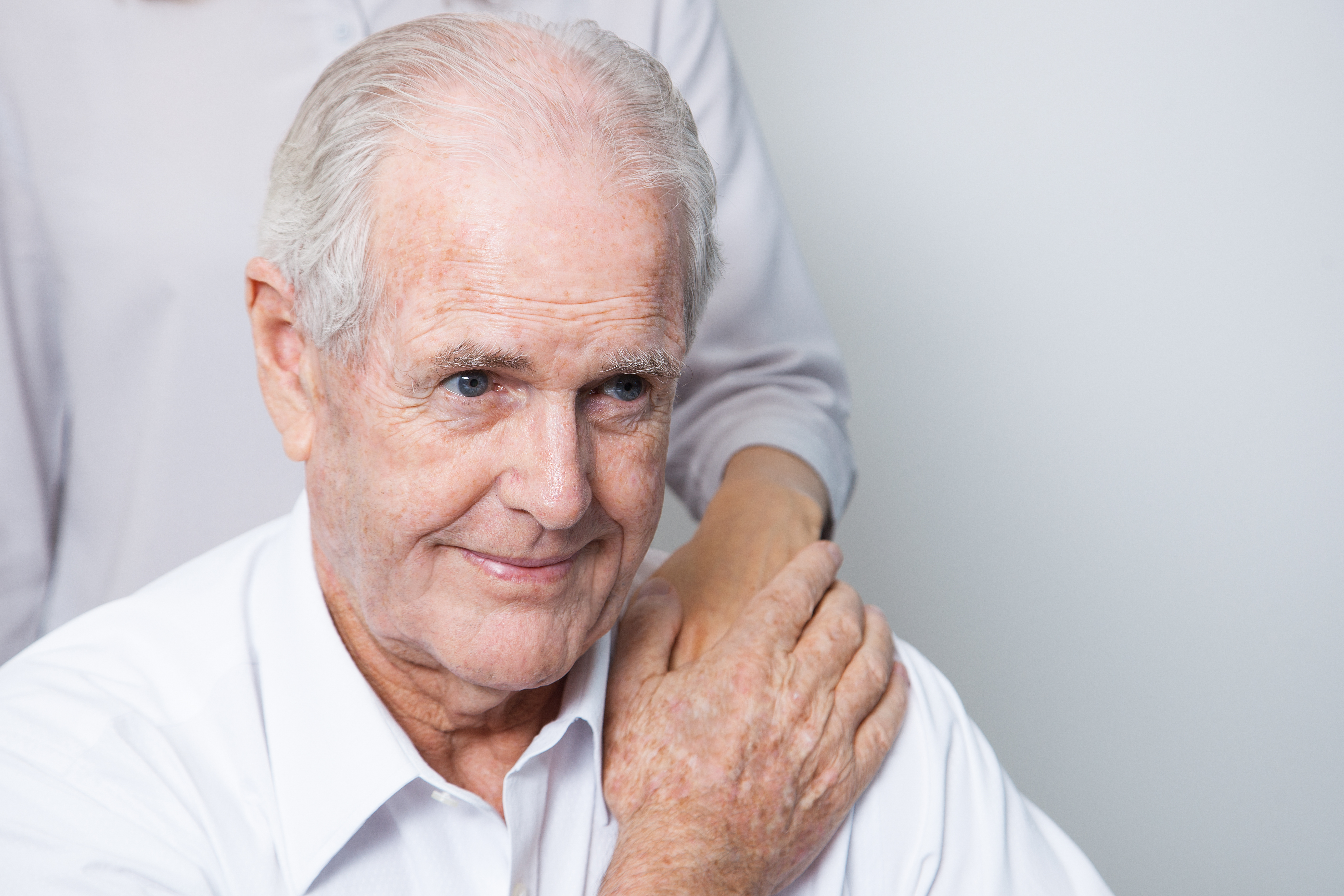 Closeup of content senior man and unrecognizable woman putting hand on his shoulder. Isolated view on white background.